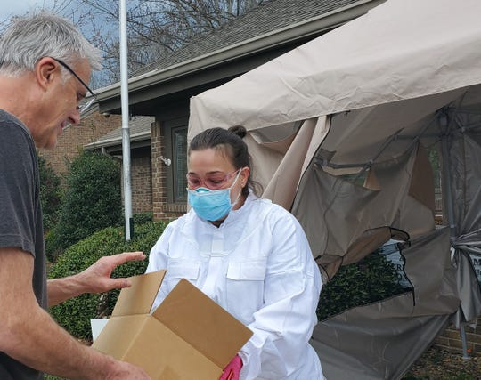 SylvanSport president Tom Dempsey delivers a supply of face masks to Wendy Alexander at Hendersonville Pediatrics last week. Dempsey's company was able to procure the face masks from a supplier in China.