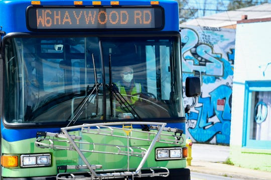 An Asheville Regional Transit driver wears a mask while driving down Haywood Road in West Asheville March 26, 2020. ART buses began limiting riders to 10, including the driver, March 25.