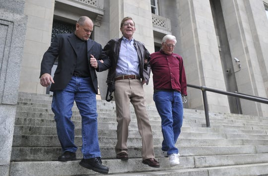 Tom Chickos, far left, former sheriff Bobby Medford, and Ron Honeycutt make their way down the steps of the federal courthouse after Medford was found guilty on all 11 charges related to illegal gambling.