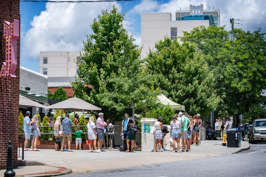 A line wraps around Wicked Weed Brewing Company in downtown Asheville on June 25, 2020. Governor Roy Cooper announced that face masks will be required state-wide indoors and outdoors where social distancing is not possible starting June 26.