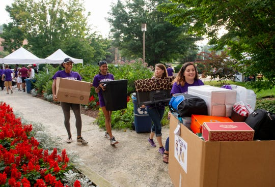 Western Carolina University student and staff volunteers march into a residence hall with a new student's belongings on Move-In Day, Friday. More than 1,500 WCU students, faculty and staff banded together to help the university's incoming freshmen move into their residence hall rooms. Classes start Monday.