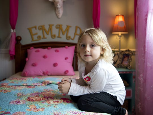 Emma, 6, crouches on her bed in her room in her parents' house in Arden. Emma began showing signs of being transgender to her parents by the age of 3.